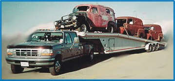 Picture of trailer  loaded with  panel trucks and Ford parts